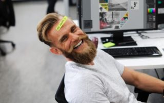 "Happy Employee at this desk with a sticky note on his forehead that says ""Be Happy"""